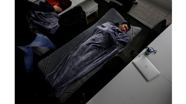 Han Liqun,un gerente de Recursos Humanos de Renren crédito Management Co., duerme en una cama plegable en la oficina después de terminar el trabajo temprano en la mañana