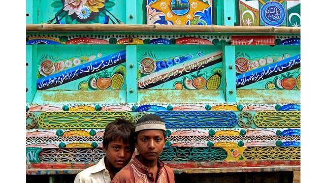 Niños posan para una foto delante de un camión decorado en Peshawar