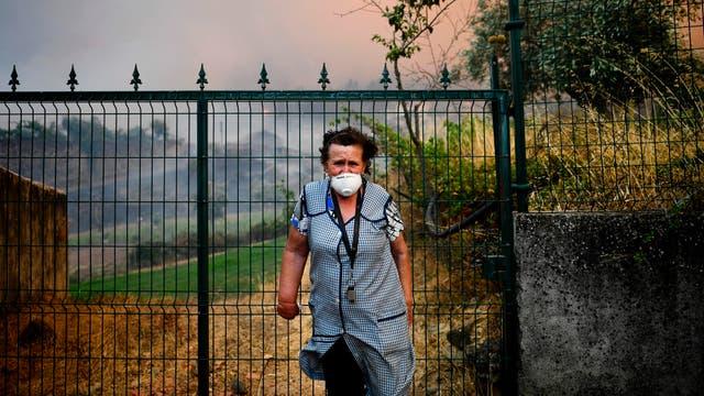 Una aldeana de Sanguinheira se encuentra frente a la puerta de su casa mientras un incendio forestal se acerca a la aldea en Macao, en el centro de Portugal.