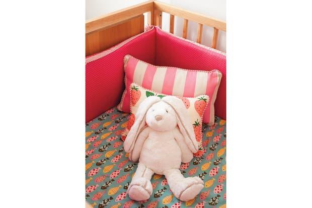 El confortable interior de la cuna con acolchado, chichonera y almohadones realizados con telas importadas (Fan) y peluche (Jellycat)..