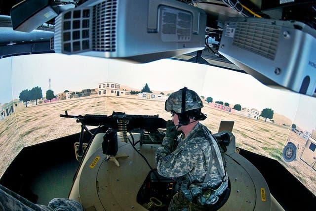 Jonathan Eddy pone a prueba un puesto de disparo desde el techo de una camioneta virtual, en uno de los tantos dispositivos de entrenamiento del ejército de EE.UU.