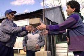 Carlos Guana y Ricardo González apilan los bloques que darán lugar a la primera casa del barrio, en la Asociación Vecinal 26 de Julio