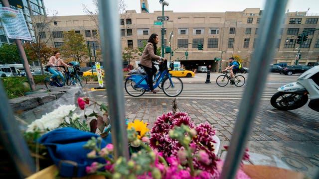Le gente pasea en los alrededores del altar conmemorativo en la ciclovia