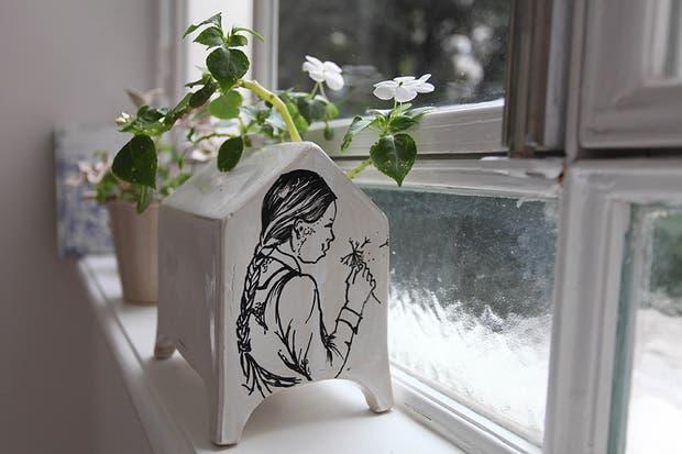 El ventanal baña de luz natural a los distintos ambientes. Delante, a modo decorativo, maceta ''casita ilustrada'' de gres ($150, Artefactos). Foto: Guadalupe Aizaga