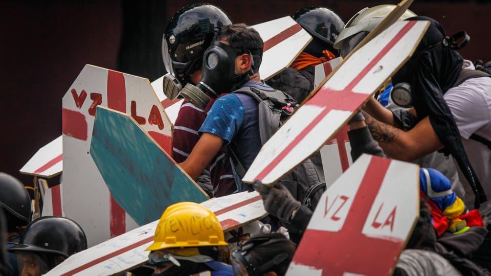 Manifestantes con escudos caseros y mascaras de gas en los enfrentamientos contra la policía antidisturbios que bloque el avance hacia la Asamblea Nacional. Foto: AP / Fernando Llano