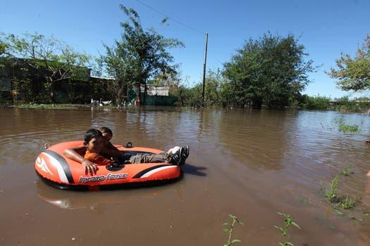 Dos niños se trasladan en un bote inflable. Foto: LA NACION / Ricardo Pristupluk
