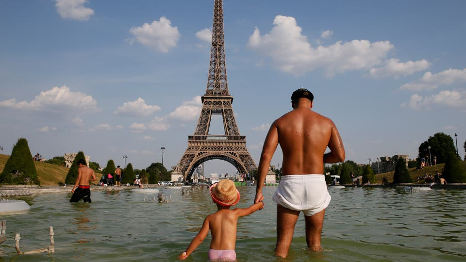 Un hombre se refresca junto a su hijo en la fuente de los jardines del Trocadero, cerca de la Torre Eiffel. Foto: Reuters