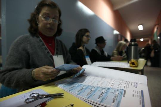Una fiscal de mesa tiene una tijera para cortar los padrones que están mal troquelados. Foto: LA NACION / Ezequiel Muñoz