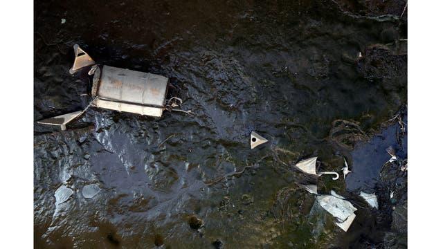 Un paraguas y otros desechos descansan en el lecho