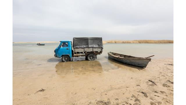 Pescadores en un camión recogen el pescado de un barco en aguas poco profundas en las afuera del pueblo de Karateren