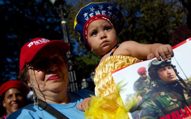 Una mujer con un niño en la entrada del Hopital Militar de Caracas donde está internado Hugo Chávez