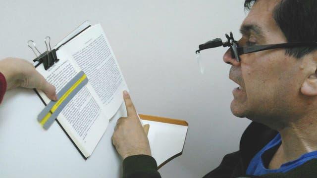 Un paciente con baja visión utilizando ayuda óptica y una guía de lectura