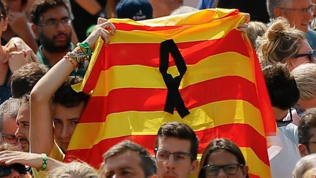 Un joven levanta una bandera catalana durante el homenaje. Foto: AP / Francisco Seco