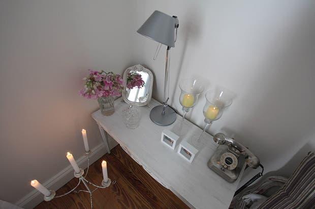 La mesa de luz es una suma de objetos que aportan calidez: flores, velas, un espejo restaurado, mini portarretratos y un teléfono antiguo que se integra a la perfección. El piso de pinotea fue pulido e hidrolaqueado. Foto: Guadalupe Aizaga