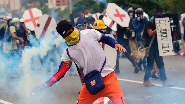 Un manifestante devuelve una bomba de gas lacrimógena en medio de una manifestación