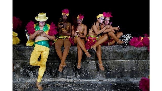 Los bailarines utilizan un punto de acceso a Internet antes de actuar en el Carnaval de La Habana