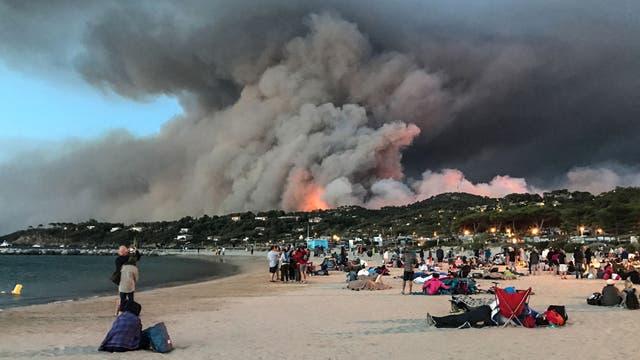 Personas evacuadas encontraron refugio en la playa y miran un incendio quemando el bosque en Bormes-les-Mimosas, al amanecer en el sur de Francia