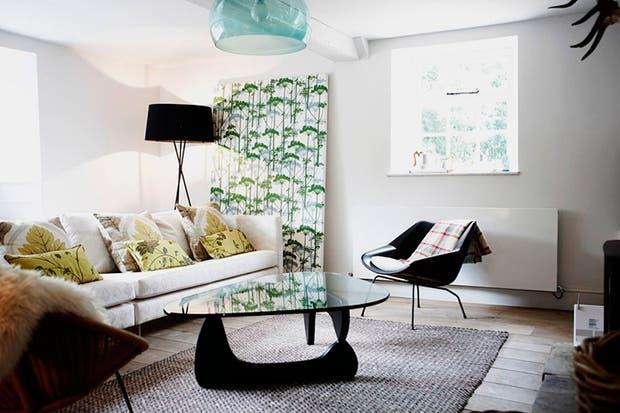En el living, la lámpara retro, el panel con motivos vegetales y los géneros de los almohadones, dan un toque vintage al ambiente..