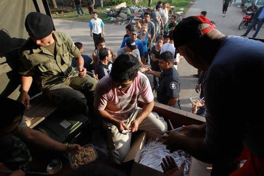 Gendarmes reparten comida en el barrio Villa Elvira. Foto: LA NACION / Fabián Marelli