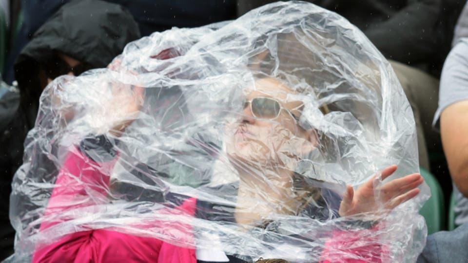 Un espectador se refugia  por lluvia  juegan en el quinto día de los campeonatos de tenis de Wimbledon en Londres, el viernes, 1 de julio de 2016.. Foto: AP / Tim Ireland