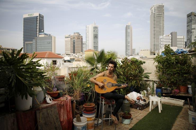 El músico Iyar Semel, de 38 años, interpreta el laud en su jardín de la azotea, donde él y sus otros dos compañeros de piso cultivan hierbas y verduras