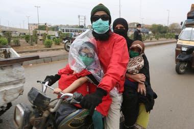 Una familia en moto, con barbijos, en Karachi, Paquistán