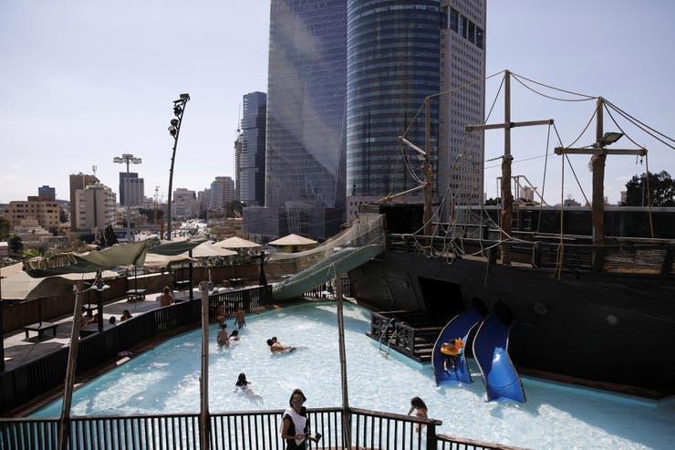 La gente se baña en la piscina de un parque de atracciones en la azotea del centro comercial Azrieli en el centro de Tel Aviv