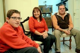 Nicolás, en el living de su casa de Córdoba, junto a sus padres, Sandra y Osvaldo