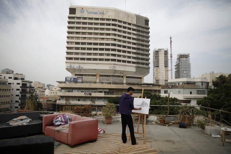 El pintor aficionado Kobi Malul, de 31 años, pinta en su azotea en el centro