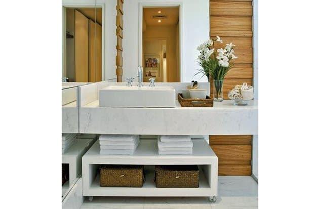 Mesada de mármol de Carrara. Debajo, consola baja de madera laqueada con ruedas.  /Casa.abril.com.br