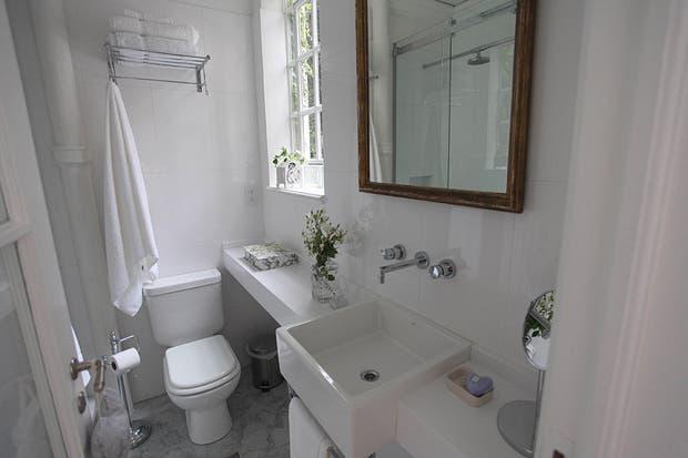 El baño combina lo antiguo con lo moderno: se mantuvieron las aberturas, el piso, las molduras y la columna de desagüe que se dejó a la vista. Aprovechando al máximo cada espacio, se colocó sobre el inodoro un rack para toallas. Foto: Guadalupe Aizaga