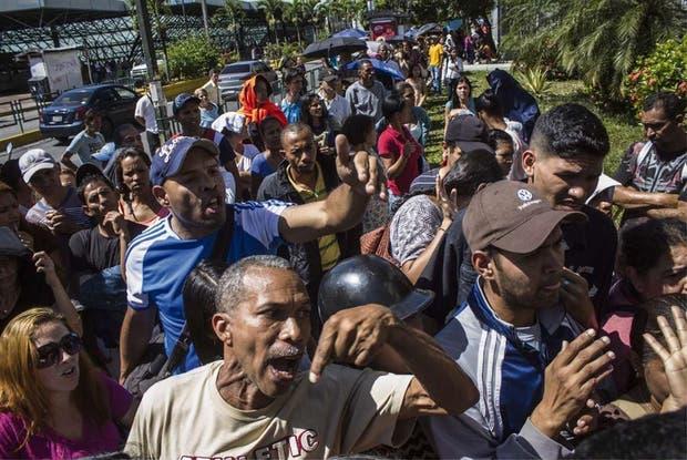 Un grupo de personas reclama que abran las puertas de un supermercado, en Caracas