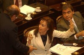 La entonces primera dama y presidenta de la Comisión de Asuntos Constitucionales, Cristina Kirchner, habla con el senador Busti durante el tratamiento de la ley antisecuestro y de los ascensos militares