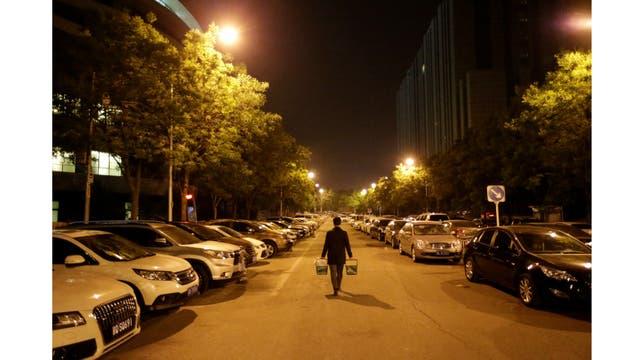 Han Liqun, un gerente de Recursos Humanos de Renren crédito Management Co., lleva cerveza y comida para sus colegas a la oficina después de la medianoche