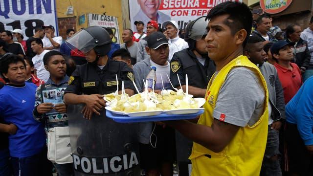 Un vendedor de comida aprovecha un intervalo durante campeonato de fútbol callejero Mundialito de El Porvenir en Lima, Perú.