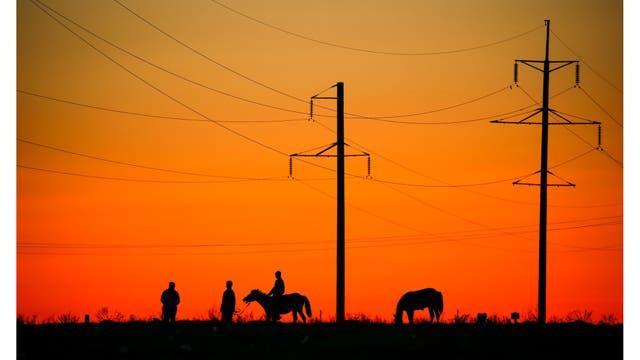 Residentes a caballos junto a las líneas eléctricas en la ciudad de Aral, al suroeste de Kazajstán