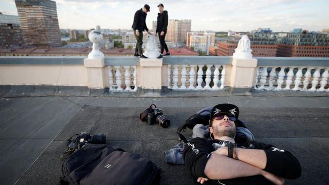Yevgeny Halkechev del equipo de Rudex descansa mientras que sus compañeros de equipo caminan por el filo de la terraza en un edificio de Moscú, Rusia,