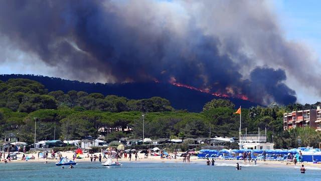 Algunas personas disfrutan de la playa mientras se incendia un bosque detrás de ellos en Bormes-les-Mimosas, sureste de Francia.
