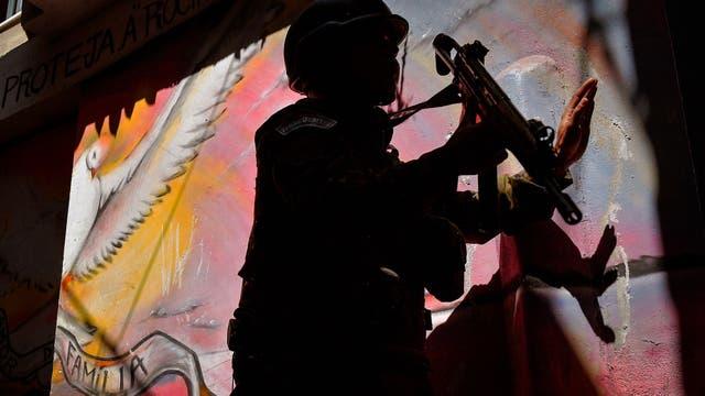 Un soldado patrulla delante de un graffiti que representa una paloma de la paz en la favela de Rocinha