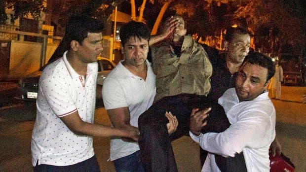 Uno de los heridos en el ataque de ayer en Dacca, al ser rescatado