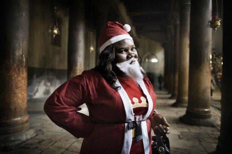 Una peregrina nigeriana disfrazada de Papá Noel que visitó la Basílica de la Natividad, en Belén. Foto: AFP