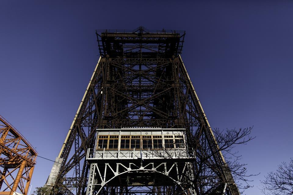 Hay solo ocho puentes transbordadores en todo el mundo, y uno de ellos es el de la Boca. Símbolo del barrio y del poderío del hierro, un ingeniero comanda su recuperación y sueña con la posibilidad de que lo declaren Patrimonio de la Humanidad