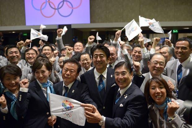 El gobernador de Tokio, el primer ministro de Japón y el CEO de la candidatura, celebran en el momento del anuncio