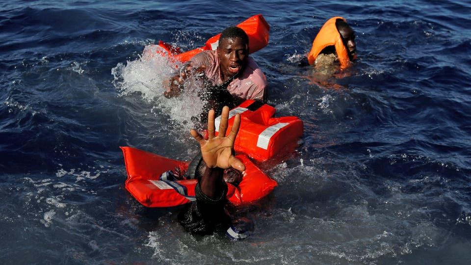 Inmigrantes tratan de mantenerse a flote luego de que su embarcación de goma se hundiera en el centro del Mediterráneo en aguas internacionales a unos 15 millas náuticas frente a la costa de Zawiya en Libia