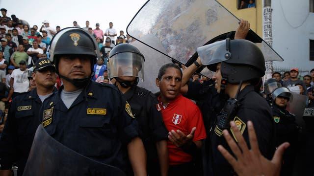 Los árbitros reciben protección especial en este evento porque la mitad de los espectadores no están de acuerdo con sus acciones, repudian tirándoles botellas y huesos de pollo, durante el campeonato de fútbol callejero Mundialito de El Porvenir en Lima, Perú.