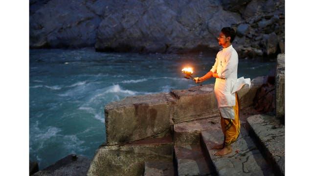 Lokesh Sharma, de 19 años, un sacerdote hindú, realiza oraciones vespertinas a orillas del río Ganges en Devprayag