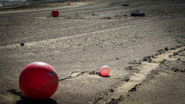 Boyas yacen sobre la arena en lugares antes tapados por el agua