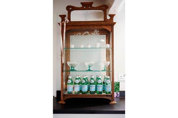 Un antiguo mueble de madera y cristal sirve para guardar la vajilla, copas y botellas..
