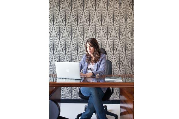 la diseñadora Carmen Niro Blanco frente al espléndido escritorio de nogal (Ohmio) acompañado por sillas Jacobsen (Manifesto) y un sillón principal, ambos elegidos en negro para que no compitieran con el resto del mobiliario.