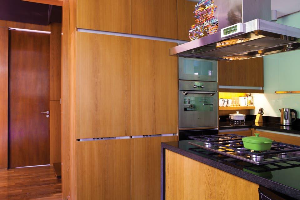 La cocina es notable por los pisos y revestimientos de madera, por la agradable y práctica circulación que propone la isla y, sobre todo, por las ventanas corredizas que se abren francamente al patio interior..